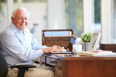 Hög man som hemma använder bärbara datorn på skrivbordet fotografering för bildbyråer