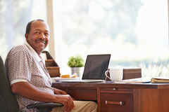 Hög man som hemma använder bärbara datorn på skrivbordet royaltyfri bild