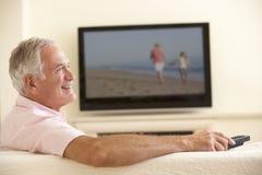 Hög man som hemma håller ögonen på Widescreen TV Fotografering för Bildbyråer