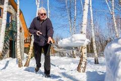 Hög man som kastar snö med skyffeln från privat husgård i vinter på ljus solig dag Äldre person som tar bort den insnöade trädgår fotografering för bildbyråer