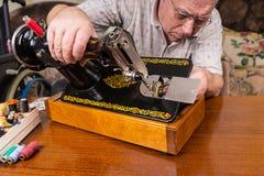 Hög man som kontrollerar den gammalmodiga symaskinen royaltyfri fotografi