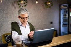 Hög man som kontrollerar tid, medan genom att använda bärbara datorn i en stång royaltyfri fotografi
