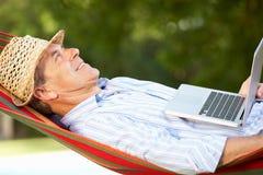 Hög man som kopplar av i hängmatta med bärbar dator Royaltyfri Bild