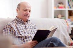 Hög man som läser en bok på hans soffa arkivfoto