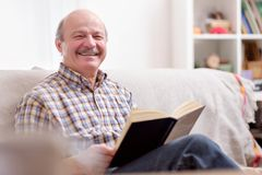 Hög man som läser en bok på hans soffa fotografering för bildbyråer
