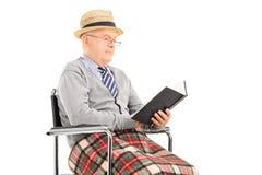 Hög man som läser en bok som placeras i rullstol Royaltyfri Foto