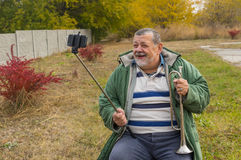 Hög man som ler, medan göra selfie som är utomhus- för online-social nätverkandeservice Royaltyfri Foto