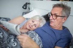 Hög man som ligger i säng med den läs- tidningen för fru royaltyfri fotografi