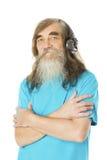 Hög man som lyssnar till musik i hörlurar Gamal man med skägget Fotografering för Bildbyråer