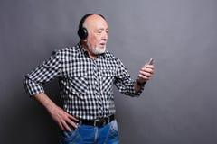 Hög man som lyssnar till musik med hörlurar Fotografering för Bildbyråer