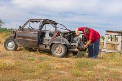 Hög man som reparerar dengjorda bilen Arkivbild