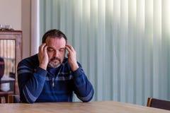 Hög man som rymmer hans händer till hans huvud med en huvudvärk fotografering för bildbyråer