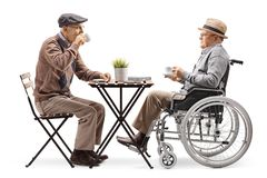 Hög man som sitter och dricker kaffe med en rörelsehindrad man i en rullstol arkivbilder