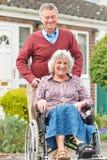 Hög man som skjuter den rörelsehindrade frun i rullstol arkivbilder