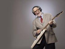 Hög man som spelar den elektriska gitarren arkivbild