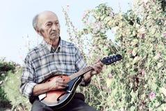 Hög man som spelar mandolinen Arkivbild