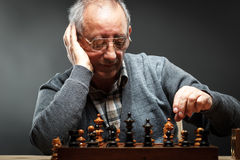 Hög man som tänker om hans nästa flyttning i en lek av schack Royaltyfria Bilder
