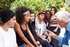 Hög man som talar med ligan av ungdomar royaltyfria bilder