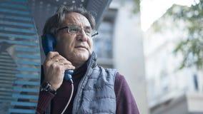 Hög man som talar på den offentliga payphonen i utomhus arkivbilder