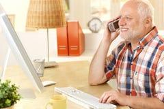 Hög man som talar på mobiltelefon, genom att använda datoren Royaltyfri Foto