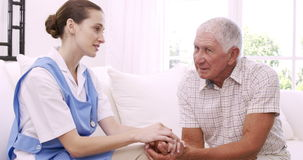 Hög man som talar till sjuksköterskan