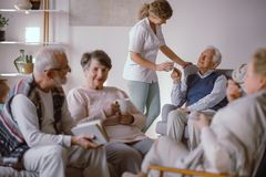 Hög man som tar en kopp te från hans anhörigvårdare i vårdhemmet royaltyfria bilder