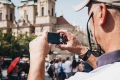 Hög man som tar foto på kamera i den gamla stadfyrkanten, Prague, Tjeckien royaltyfri foto