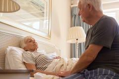 Hög man som tar omsorg av hans sjuka fru i säng arkivbild
