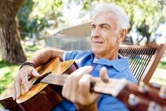Hög man som utomhus plying gitarren arkivbilder