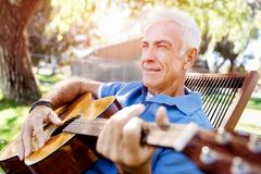 Hög man som utomhus plying gitarren arkivfoton