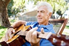 Hög man som utomhus plying gitarren royaltyfri bild