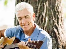 Hög man som utomhus plying gitarren arkivfoto