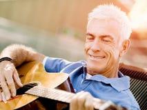 Hög man som utomhus plying gitarren Arkivbild