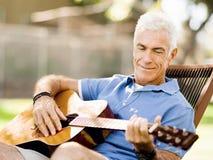 Hög man som utomhus plying gitarren Royaltyfri Foto
