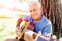 Hög man som utomhus plying gitarren fotografering för bildbyråer