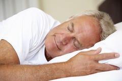 Hög man sovande i säng royaltyfri fotografi