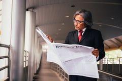 Hög manlig affärsledare som läser den traditionella tidningen utanför företaget arkivfoton