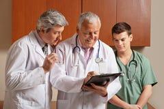 Hög manlig doktor With Colleagues Fotografering för Bildbyråer