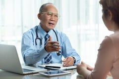 Hög manlig doktor i blå skjorta som talar med den kvinnliga patienten royaltyfria bilder