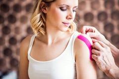 Hög manlig fysioterapeut som applicerar bandet på en kvinnlig patient close upp arkivbilder