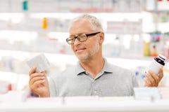 Hög manlig kund som väljer droger på apotek fotografering för bildbyråer