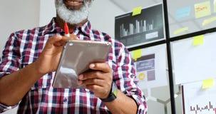 Hög manlig ledare som använder den digitala minnestavlan 4k lager videofilmer