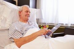 Hög manlig patient som använder den Digital minnestavlan i sjukhussäng royaltyfria foton