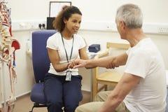 Hög manlig patient som har sjukgymnastik i sjukhus royaltyfria foton