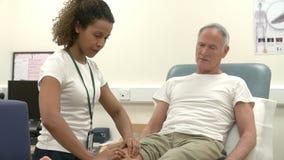 Hög manlig patient som har sjukgymnastik i sjukhus lager videofilmer