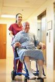 Hög manlig patient som skjuts i rullstol av sjuksköterskan arkivbilder