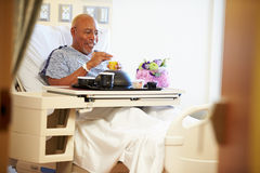 Hög manlig patient som tycker om mål i sjukhussäng Fotografering för Bildbyråer