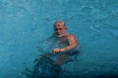 Hög manlig simning i simbassäng royaltyfri foto