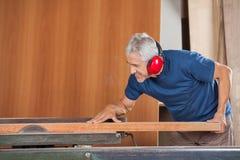 Hög manlig snickare Cutting Wooden Plank med royaltyfri bild