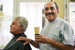 Hög manworking som barberare i hårsalong Arkivbild